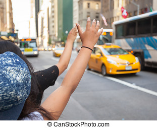 Tourists call a yellow cab in Manhattan with typical gesture