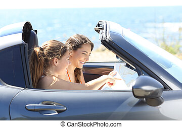 Tourists checking guide inside a car on vacations