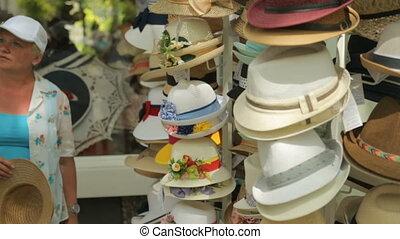 Tourists choosing hats on street market