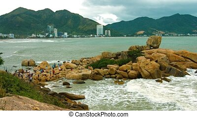 Tourists explore and climb over the massive boulders of Hon Chong Rocks, a popular attraction in Nha Trang, Vietnam. Video UltraHD