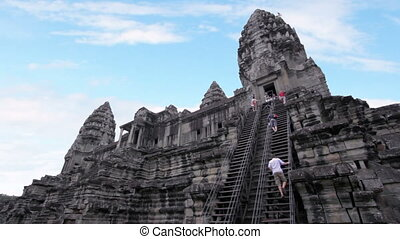 Tourists climbing angkor wat temple