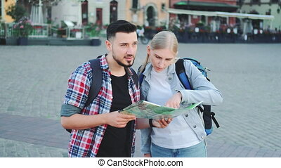 Tourists couple holding map for finding new interesting place for sightseeing. They standing on city square.