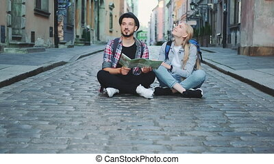 Tourists couple with map sitting on pavement and admiring historical surroundings. They are excited and smiled.