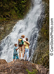 Tourists family looking at a waterfall in the mountains of Thail