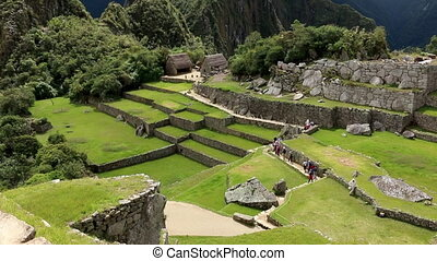 Tourists gathering towards huts on Machu Picchu - Pespective...
