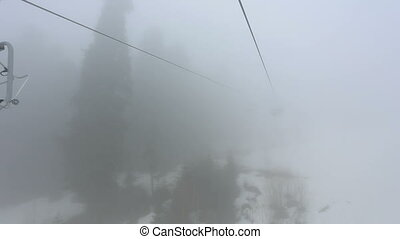Tourists go in cabins on the ropeway through fog. Early...