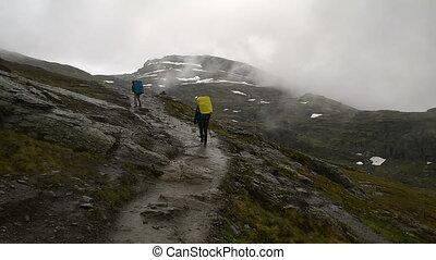 Tourists go on among the rocks. Path to the famous landmark...
