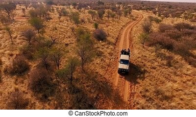 Tourists go on savannah during a safari on a hunting off-road car.