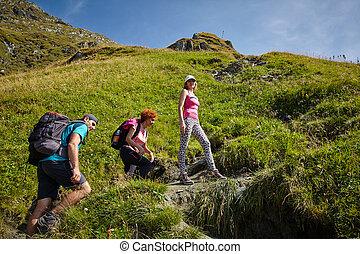 Tourists hiking on mountain trail