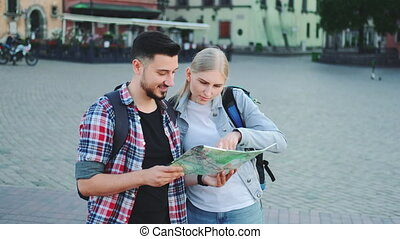 Tourists holding map and looking for some place on city square. They going sightseeing.