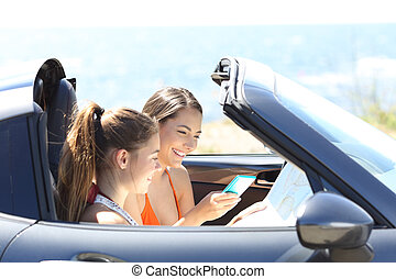 Tourists in a convertible car searching destination online