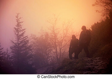 Tourists in fog in mountains.