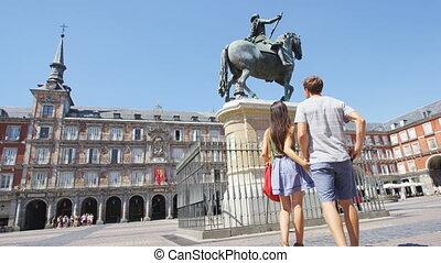 Tourists in Madrid Spain on Plaza Mayor walking holding ...
