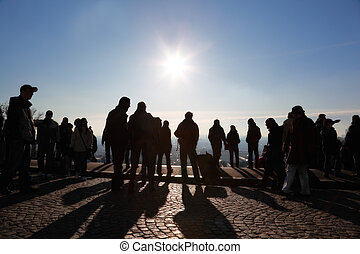 Tourists in Paris looking at panorama of city on observation platform