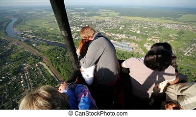Tourists look at city and photograph it from flying balloon
