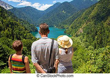 Tourists looking at mountain lake