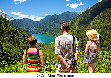 Tourists looking at mountain lake Rizza