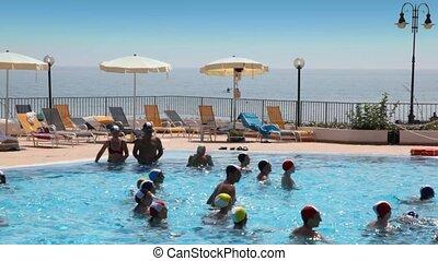 Tourists make  waterobics in pool near beach