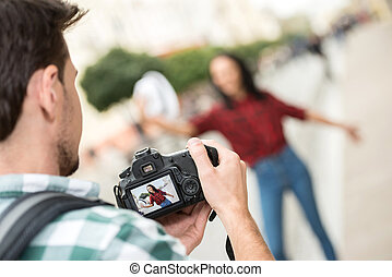 Tourists - Man is taking picture of girlfriend on tourist...