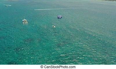 Tourists on a parachute over the sea. Boracay, Philippines