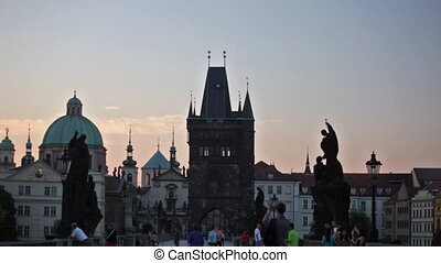 Tourists on Charles Bridge early in the morning at sunrise, Prague