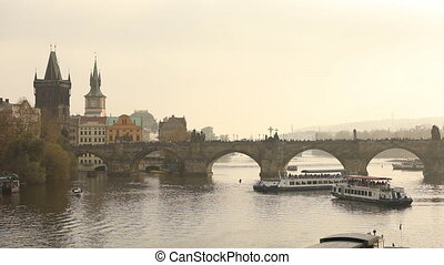 Tourists on Charles bridge, Prague against the backdrop of a tourist ship at sunset, general plan