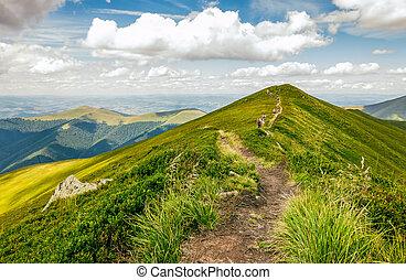 tourists on footpath through the mountain ridge - summer...