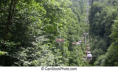 tourists on moving funicular above mountain forest