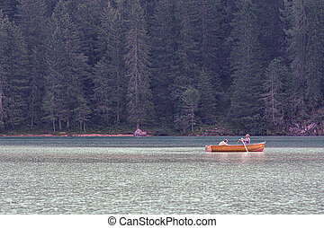 Tourists paddle on a wooden boat on Lake Braies