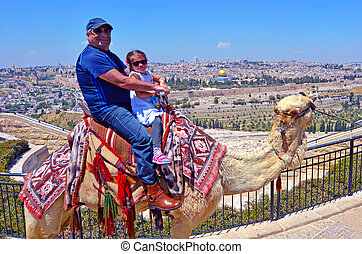 Tourists (grandfather and his grandchild)m ride a camel against temple mount in the old city of Jerusalem, Israel.