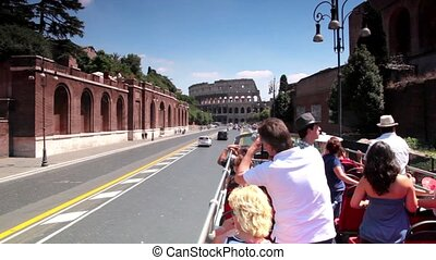 Tourists ride in an open bus on the way leading to the Coliseum