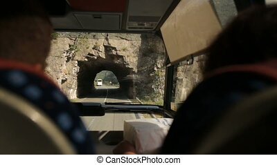 Tourists ride on the road through the rock in a bus in...
