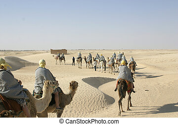 Group of tourists dressed like bedouins riding camels in line thorough Sahara desert in Tunisia