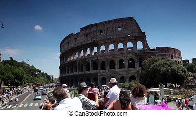 Tourists riding in an open bus on the way past the Coliseum...