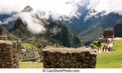 Tourists roaming around structures on Machu Picchu - Panning...