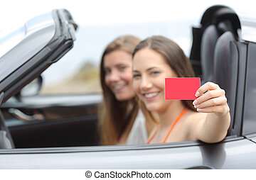 Tourists showing a blank credit card in a car