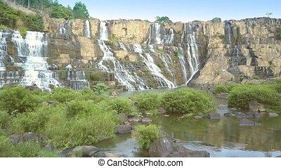 tourists sit among brushwoods watch Pongour waterfall