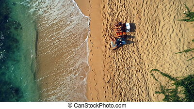 Tourists sitting together at beach 4k - Aerial view of...