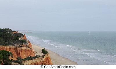 Tourists stroll along beach Falesia Vilamoura Portugal. Faro...