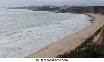 Tourists stroll along the beach Falesia Vilamoura Portugal....