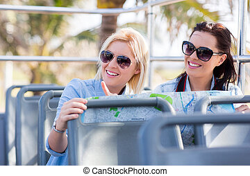 tourists taking open top bus touring the city