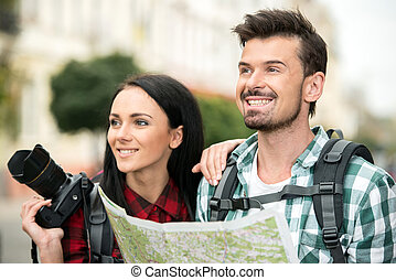 Two happy young tourists with backpacks, touristic map and camera. Sightseeing City.