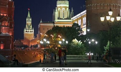 Tourists walk by Manezhnaya square near kremlin in Moscow at night