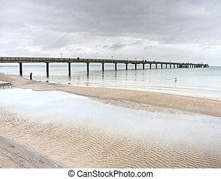 Tourists walk on sandy beach, enjoy view from wooden sea bridge