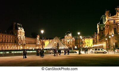 Tourists walk on square in front of Louvre - PARIS -...
