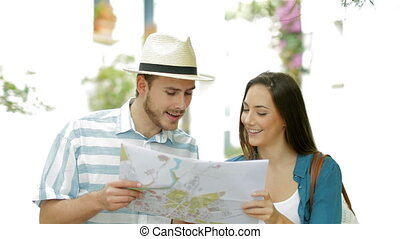 Tourists walking consulting a guide on vacation - Couple of...