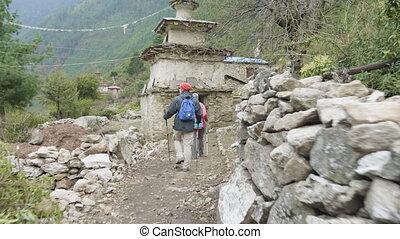 Tourists walking in nepalese village Prok, trek around ...