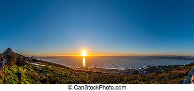 Tourists watching the sunset from Signal Hill, Cape Town (South Africa)