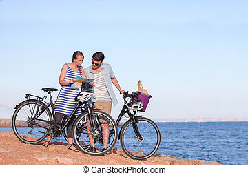 tourists with bikes looking at map in Spain.