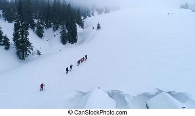 Touristse hiking in the mountains in winter - Aerial view of...